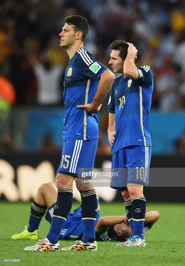 Martin Demichelis (L) and Lionel Messi of Argentina look on after being defeated by Germany 1-0 in extra time during the 2014 FIFA World Cup Brazil Final match between Germany and Argentina at Maracana on July 13, 2014 in Rio de Janeiro, Brazil.