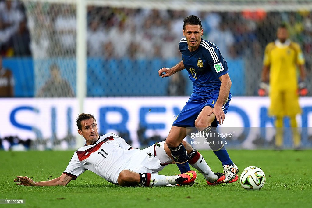 Martin Demichelis of Argentina and Miroslav Klose of Germany compete for the ball during the 2014 FIFA World Cup Brazil Final match between Germany and Argentina at Maracana on July 13, 2014 in Rio de Janeiro, Brazil.