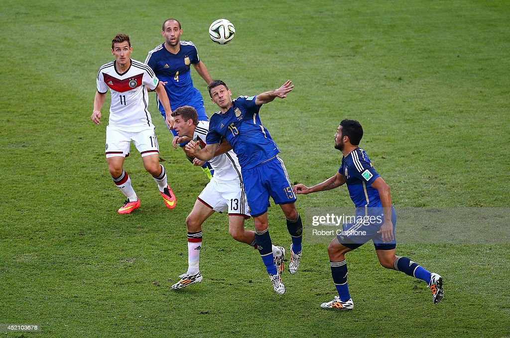 Martin Demichelis of Argentina and Thomas Mueller of Germany compete for the ball during the 2014 FIFA World Cup Brazil Final match between Germany and Argentina at Maracana on July 13, 2014 in Rio de Janeiro, Brazil.