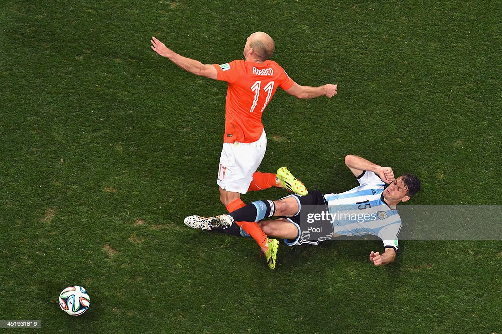 Martin Demichelis of Argentina tackles Arjen Robben of the Netherlands during the 2014 FIFA World Cup Brazil Semi Final match between the Netherlands and Argentina at Arena de Sao Paulo on July 9, 2014 in Sao Paulo, Brazil.
