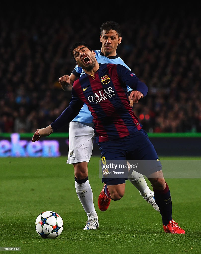 Martin Demichelis of Manchester City challenges Luis Suarez of Barcelona during the UEFA Champions League Round of 16 second leg match between Barcelona and Manchester City at Camp Nou on March 18, 2015 in Barcelona, Spain.