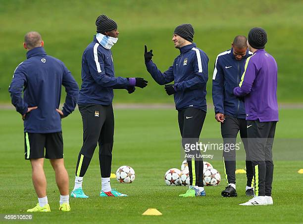 Martin Demichelis of Manchester City jokes with Yaya Toure during a training session at the Manchester City Football Academy on November 24 2014 in...