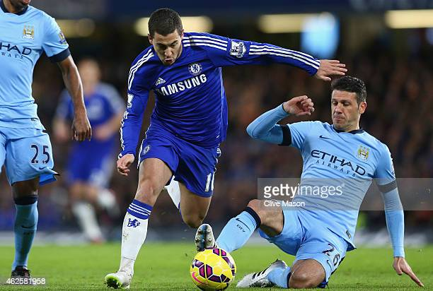 Martin Demichelis of Manchester City slides in to tackle Eden Hazard of Chelsea during the Barclays Premier League match between Chelsea and...