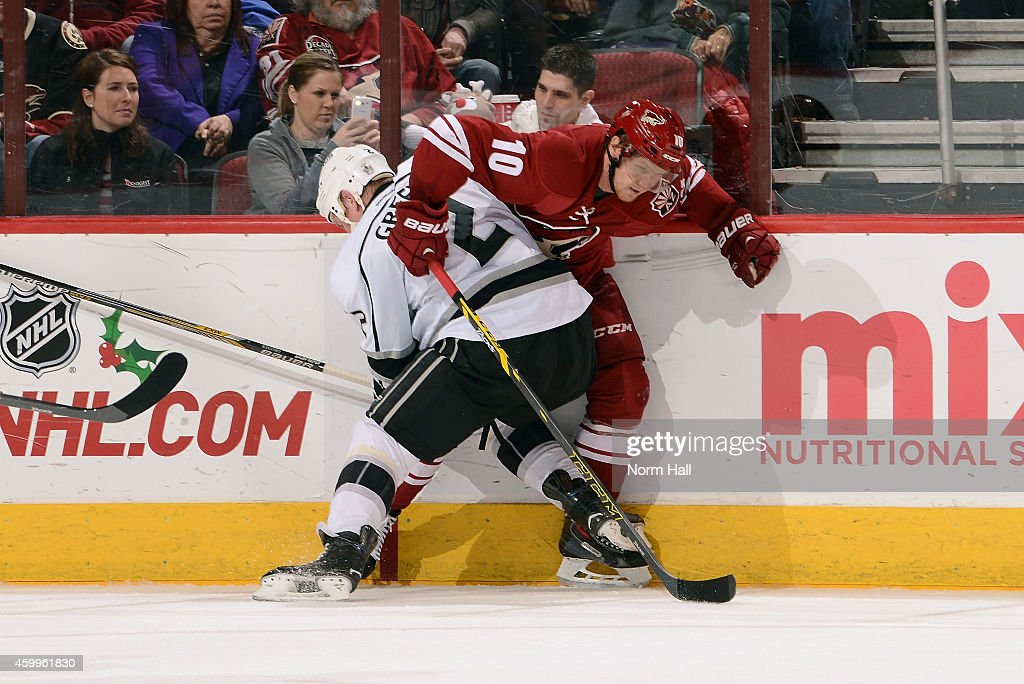 Martin Erat #10 of the Arizona Coyotes is checked into the boards by Matt Greene #2 of the Los Angeles Kings during the first period at Gila River Arena on December 4, 2014 in Glendale, Arizona.