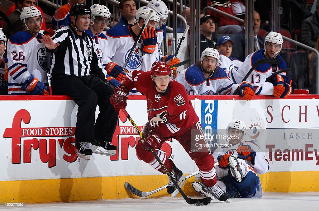 Martin Erat #10 of the Arizona Coyotes skates with the puck ahead of Jordan Eberle #14 of the Edmonton Oilers during the overtime period of the NHL game at Gila River Arena on December 16, 2014 in Glendale, Arizona. The Coyotes defeated the Oilers 2-1 in overtime.
