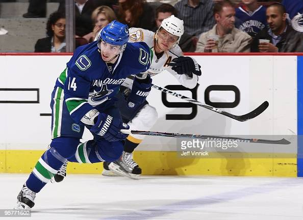 Martin Erat of the Nashville Predators and Alex Burrows of the Vancouver Canucks skate up ice during their game at General Motors Place on January 11...