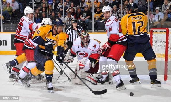 Martin Erat of the Nashville Predators battles for a loose puck against goalie Justin Peters of the Carolina Hurricanes at the Bridgestone Arena on...