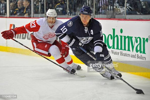 Martin Erat of the Nashville Predators skates away from Brad Stuart of the Detroit Red Wings during an NHL game on March 19 2011 at Bridgestone Arena...