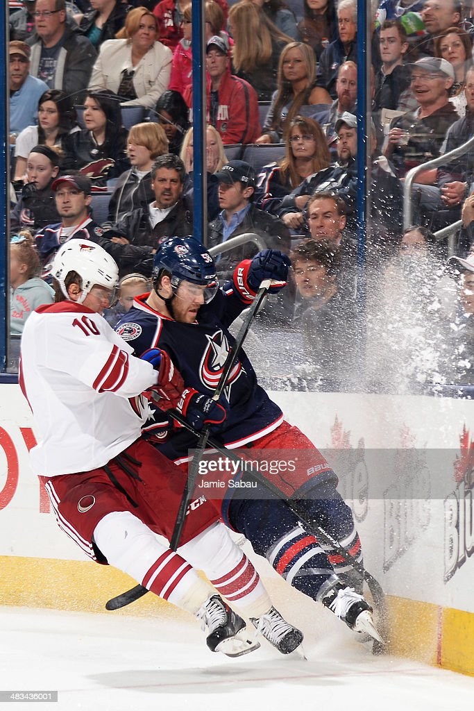 Martin Erat #10 of the Phoenix Coyotes and David Savard #58 of the Columbus Blue Jackets battle for a loose puck during the second period on April 8, 2014 at Nationwide Arena in Columbus, Ohio.