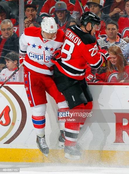 Martin Erat of the Washington Capitals and Anton Volchenkov of the New Jersey Devils come together at the boards during the game at the Prudential...