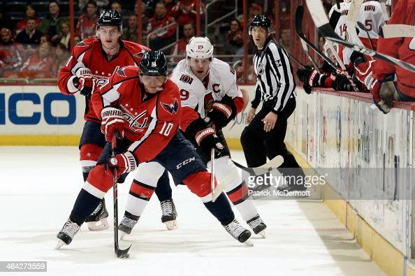 Martin Erat of the Washington Capitals brings the puck up ice as he is pursued by Jason Spezza of the Ottawa Senators in the second period during an...
