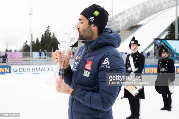 Martin Fourcade from France poses for photographers with the trophy for overall victory after he won the IBU Biathlon World Cup Men 15 km Mass Start...