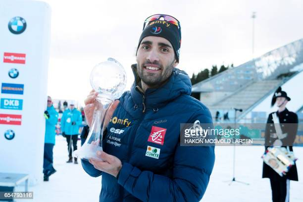 Martin Fourcade from France poses with the trophy for overall victory in IBU Biathlon World Cup Biathlon Men pursuit in Oslo on March 18 2017 / AFP...