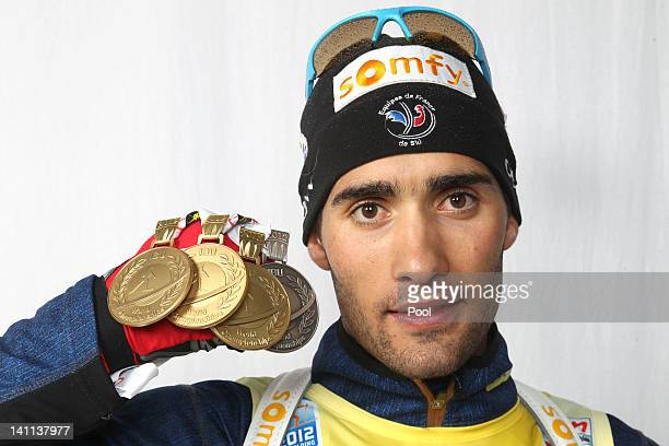 Martin Fourcade of France shows his medals of the IBU Biathlon World Championships Men's Mass Start on March 11 2012 in Ruhpolding Germany