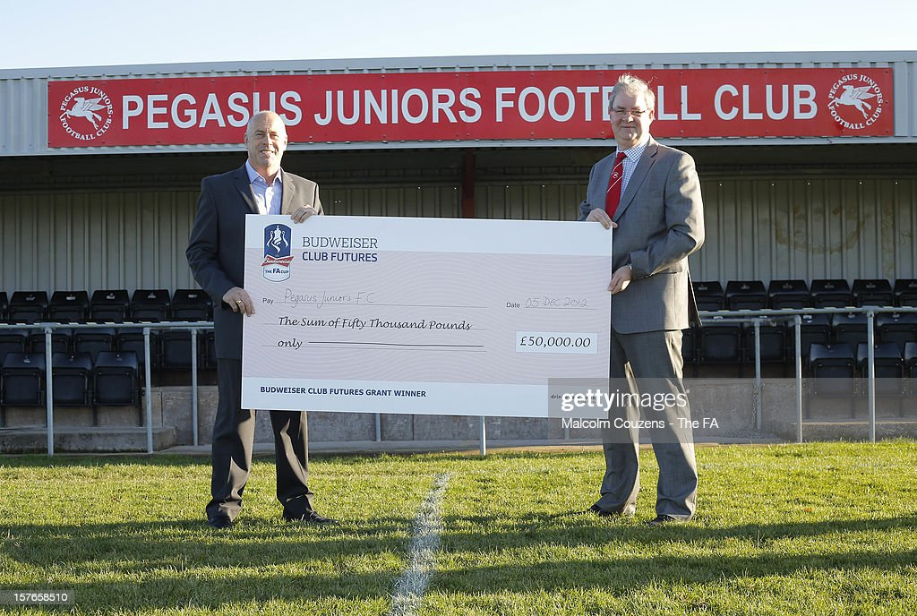 Martin Foyle (left) the regional Club Futures ambassador for the West Midlands pictured in front of the main stand with Kevin Bishop, chief executive of Pegasus Juniors FC, with their winning cheque during the Bud Club Futures event at Pegasus Juniors FC on December 5, 2012 in Hereford, England. Football life is set to change for Pegasus Juniors as Newcastle United boss Alan Pardew, Budweiser and the FA have today announced the winners of the £50,000 grants as part of the Budweiser Club Futures Programme. Pegasus Juniors FC to redevelop clubhouse through £50k cash injection from grass roots football programme.