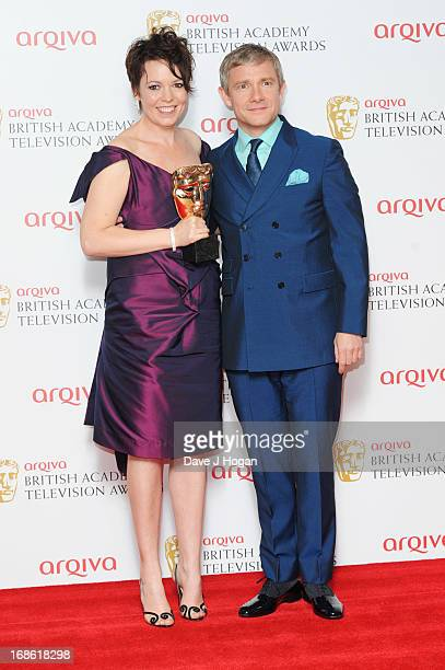 Martin Freman poses with Olivia Colman after presenting her with the Best Supporting Actress Award in front of the winners boards at the BAFTA TV...