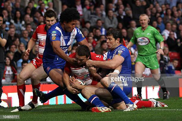 Martin Gleeson of Wigan Warriors holds off Paul Wellens and Francis Meli to dive over the line for the opening try during the engage Super League...