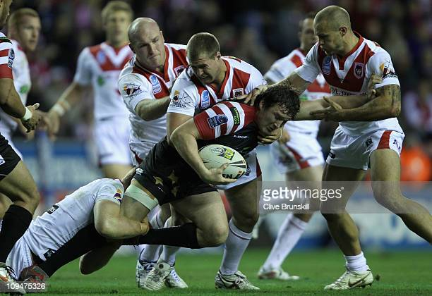 Martin Gleeson of Wigan Warriors is tackled by Ben Creagh and Trent Merrin of St George Illawarra Dragons during the World Club Challenge match...