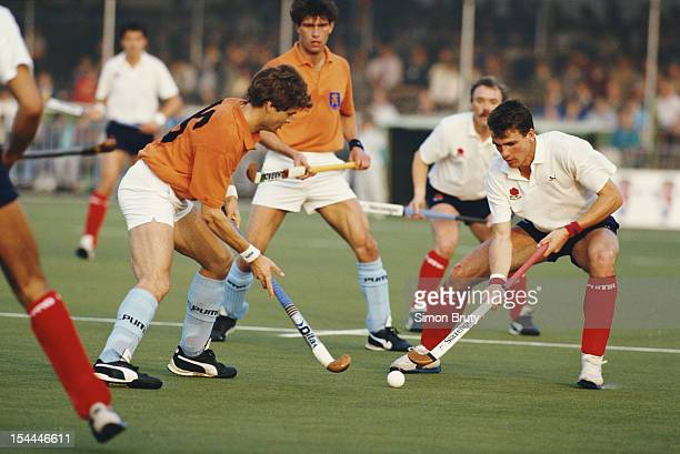 Martin Grimley of England makes a tackle on Maarten van Grimbergen of the Netherlands during their match at the 6th FIH Men's Field Hockey World Cup...