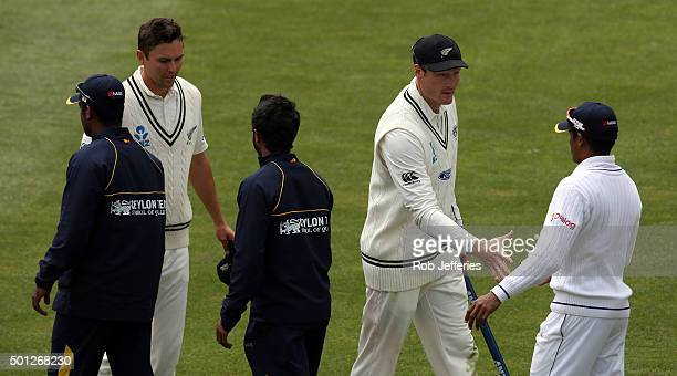 Martin Guptill and Trent Boult of New Zealand shake hands with the Sri Lanka players after winning the first test on day five of the First Test match...