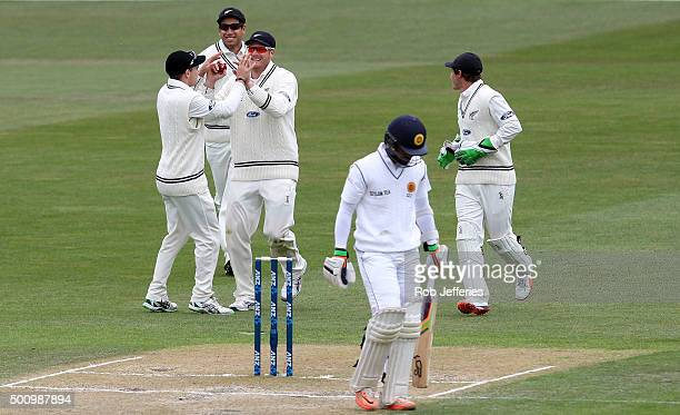 Martin Guptill of New Zealand celebrates taking a catch with Tom Latham Ross Taylor and BJ Watling to dismiss Dinesh Chandimal of Sri Lanka during...