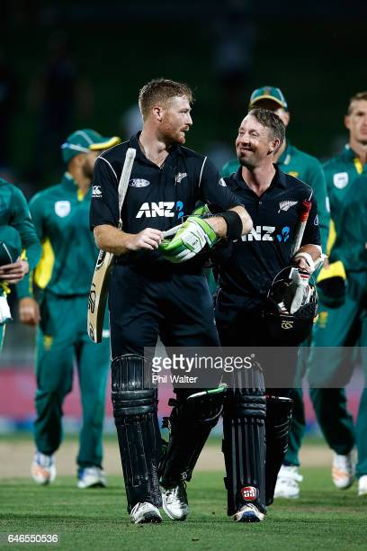 Martin Guptill of New Zealand leaves the field with Luke Ronchi following game four of the One Day International series between New Zealand and South...