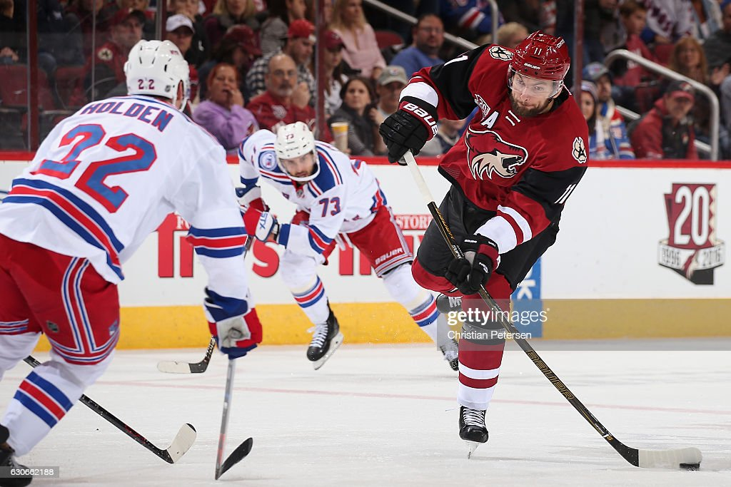 Martin Hanzal #11 of the Arizona Coyotes shoots the puck ahead of Brandon Pirri #73 and Antti Raanta #32 of the New York Rangers during the first period of the NHL game at Gila River Arena on December 29, 2016 in Glendale, Arizona.