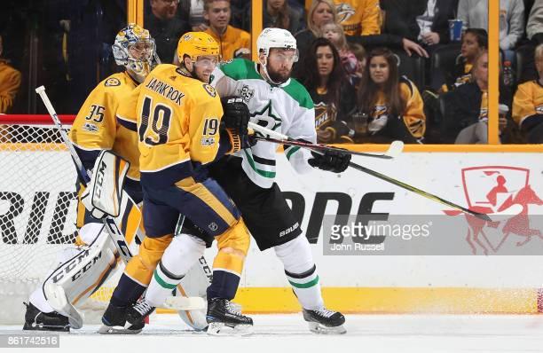 Martin Hanzal of the Dallas Stars battles in front of goalie Pekka Rinne against Calle Jarnkrok of the Nashville Predators during an NHL game at...