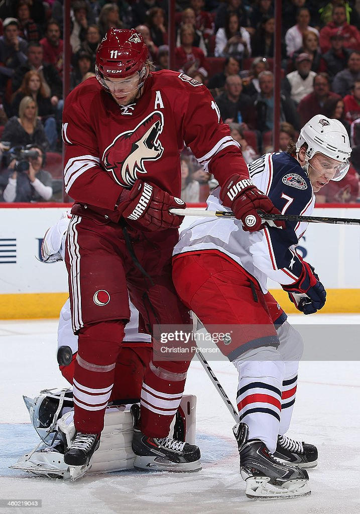 Martin Hanzal #11 of the Phoenix Coyotes attempts a deflection on the puck defended by Jack Johnson #7 of the Columbus Blue Jackets during the first period of the NHL game at Jobing.com Arena on January 2, 2014 in Glendale, Arizona.
