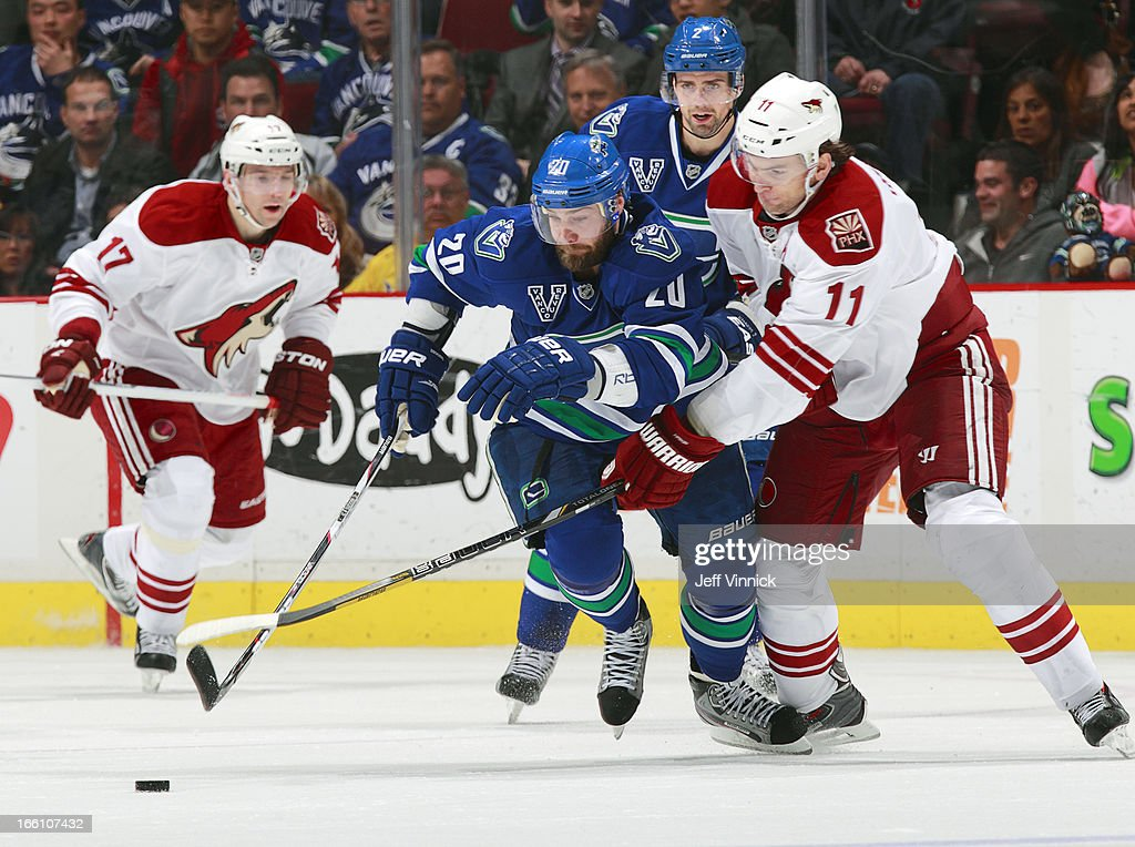 Martin Hanzal #11 of the Phoenix Coyotes checks Chris Higgins #20 of the Vancouver Canucks in front of Dan Hamhuis #2 of the Canucks and Radim Vrbata #17 of the Coyotes during their NHL game at Rogers Arena April 8, 2013 in Vancouver, British Columbia, Canada.