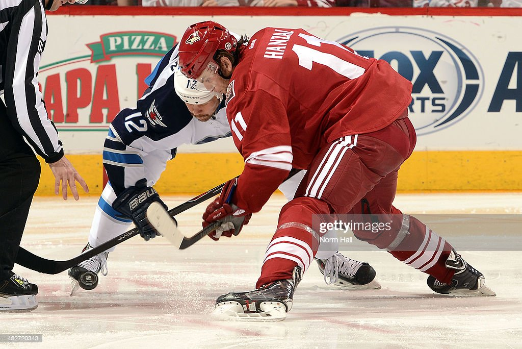 <a gi-track='captionPersonalityLinkClicked' href=/galleries/search?phrase=Martin+Hanzal&family=editorial&specificpeople=2109469 ng-click='$event.stopPropagation()'>Martin Hanzal</a> #11 of the Phoenix Coyotes takes a faceoff against <a gi-track='captionPersonalityLinkClicked' href=/galleries/search?phrase=Olli+Jokinen&family=editorial&specificpeople=202946 ng-click='$event.stopPropagation()'>Olli Jokinen</a> #12 of the Winnipeg Jets at Jobing.com Arena on April 1, 2014 in Glendale, Arizona.