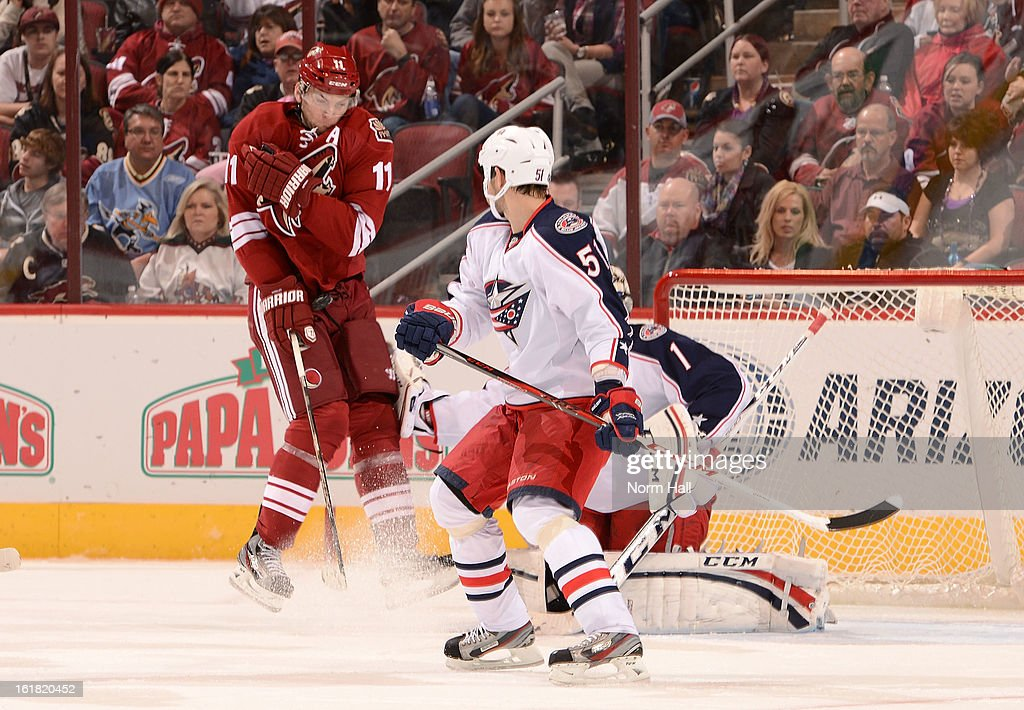 <a gi-track='captionPersonalityLinkClicked' href=/galleries/search?phrase=Martin+Hanzal&family=editorial&specificpeople=2109469 ng-click='$event.stopPropagation()'>Martin Hanzal</a> #11 of the Phoenix Coyotes takes a shot off his shoulder as he positions himself in front of goalie Steve Mason #1 and <a gi-track='captionPersonalityLinkClicked' href=/galleries/search?phrase=Fedor+Tyutin&family=editorial&specificpeople=215245 ng-click='$event.stopPropagation()'>Fedor Tyutin</a> #51 of the Columbus Blue Jackets during the second period at Jobing.com Arena on February 16, 2013 in Glendale, Arizona.