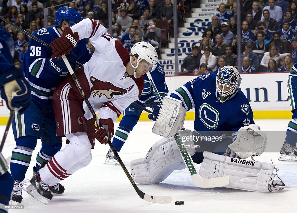 Martin Hanzal #11 of the Phoenix Coyotes tries to get a shot on goalie Cory Schneider #35 of the Vancouver Canucks while being checked by Jannik Hansen #36 of the Canucks during the first period in NHL action on April 08, 2013 at Rogers Arena in Vancouver, British Columbia, Canada.