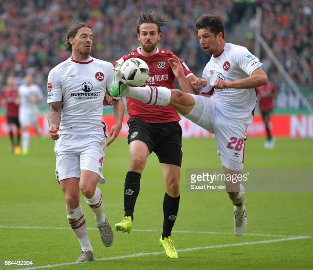 Martin Harnik of Hannover is challenged by Lukas Mhl and Dave Bulthuis of Nuernberg during the Second Bundesliga match between Hannover 96 and 1 FC...