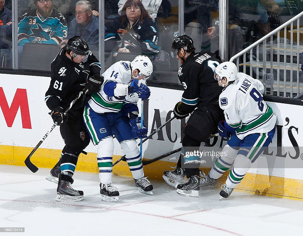 Martin Havlat #9 and Justin Braun #61 of the San Jose Sharks fight for the puck against Alexandre Burrows #14 and Christopher Tanev #8 of the Vancouver Canucks during an NHL game on January 27, 2013 at HP Pavilion in San Jose, California.