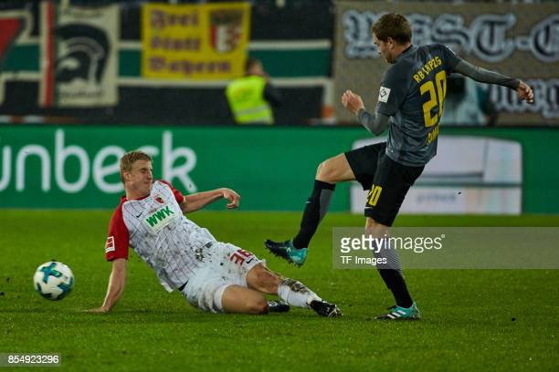 Martin Hinteregger of Augsburg and Benno Schmitz of Leipzig battle for the ball during the Bundesliga match between FC Augsburg and RB Leipzig at...