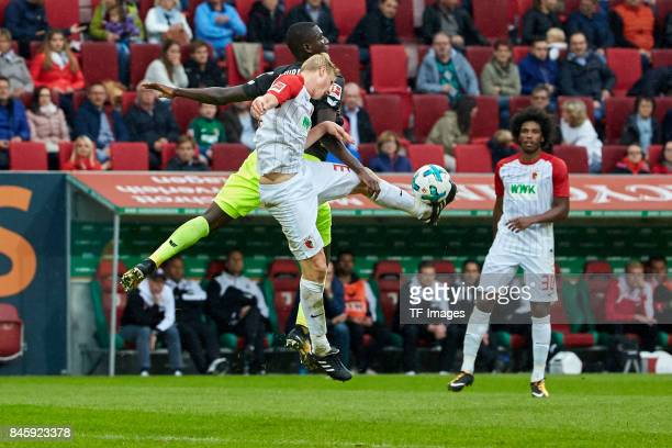 Martin Hinteregger of Augsburg and Jhon Cordoba of Koeln battle for the ball during the Bundesliga match between FC Augsburg and 1 FC Koeln at...