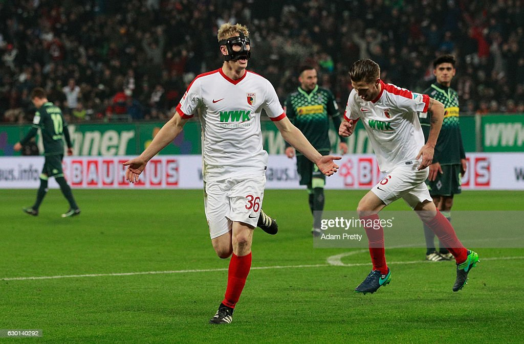 Martin Hinteregger of Augsburg celebrates with Jeffrey Gouweleeuw after scoring a goal during the Bundesliga match between FC Augsburg and Borussia Moenchengladbach at WWK Arena on December 17, 2016 in Augsburg, Germany.