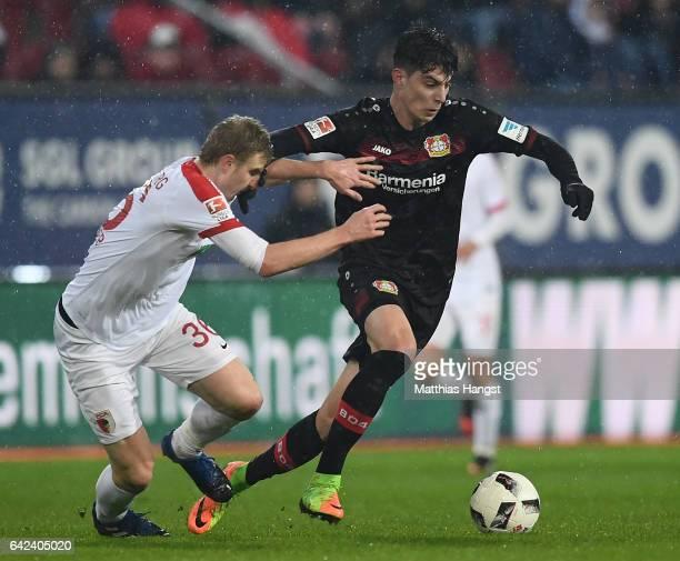 Martin Hinteregger of Augsburg challenges Kai Havertz of Leverkusen during the Bundesliga match between FC Augsburg and Bayer 04 Leverkusen at WWK...