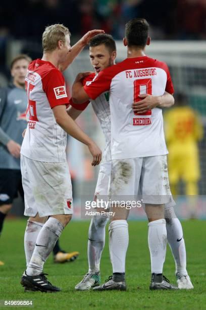 Martin Hinteregger of Augsburg Jeffrey Gouweleeuw of Augsburg and Rani Khedira of Augsburg embrace after the Bundesliga match between FC Augsburg and...