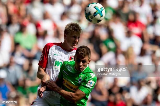 Martin Hinteregger of FC Augsburg and Thorgan Hazard of Borussia Moenchengladbach battle for the ball during a Bundesliga match between FC Augsburg...