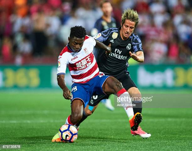 Martin Hongla of Granada CF competes for the ball with Fabio Coentrao of Real Madrid CF during the La Liga match between Granada CF v Real Madrid CF...