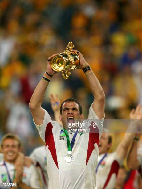 Martin Johnson the captain of England celebrates with the Webb Ellis trophy after England's victory in the Rugby World Cup Final match between...