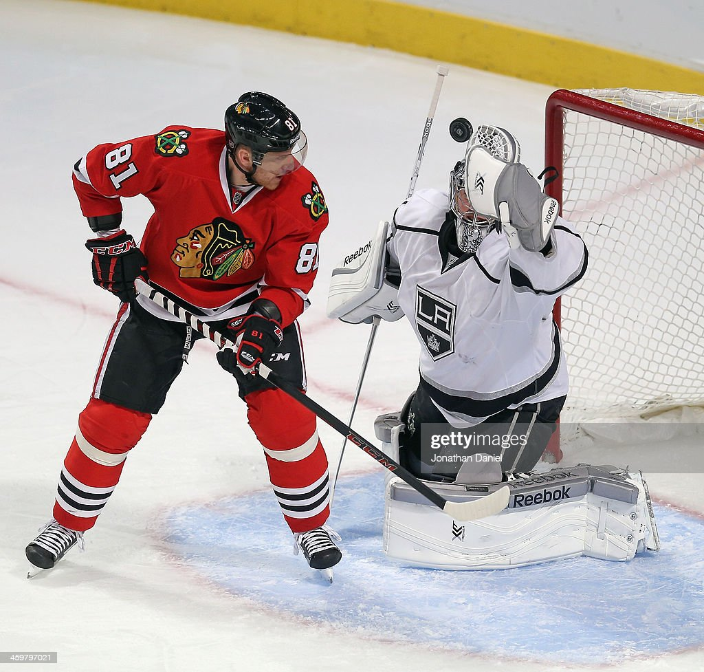 Martin Jones #31 of the Los Angeles Kings clears the puck against <a gi-track='captionPersonalityLinkClicked' href=/galleries/search?phrase=Marian+Hossa&family=editorial&specificpeople=202233 ng-click='$event.stopPropagation()'>Marian Hossa</a> #81 of the Chicago Blackhawks as the puck slips away at the United Center on December 30, 2013 in Chicago, Illinois. The Blackhawks defeated the Kings 1-0.