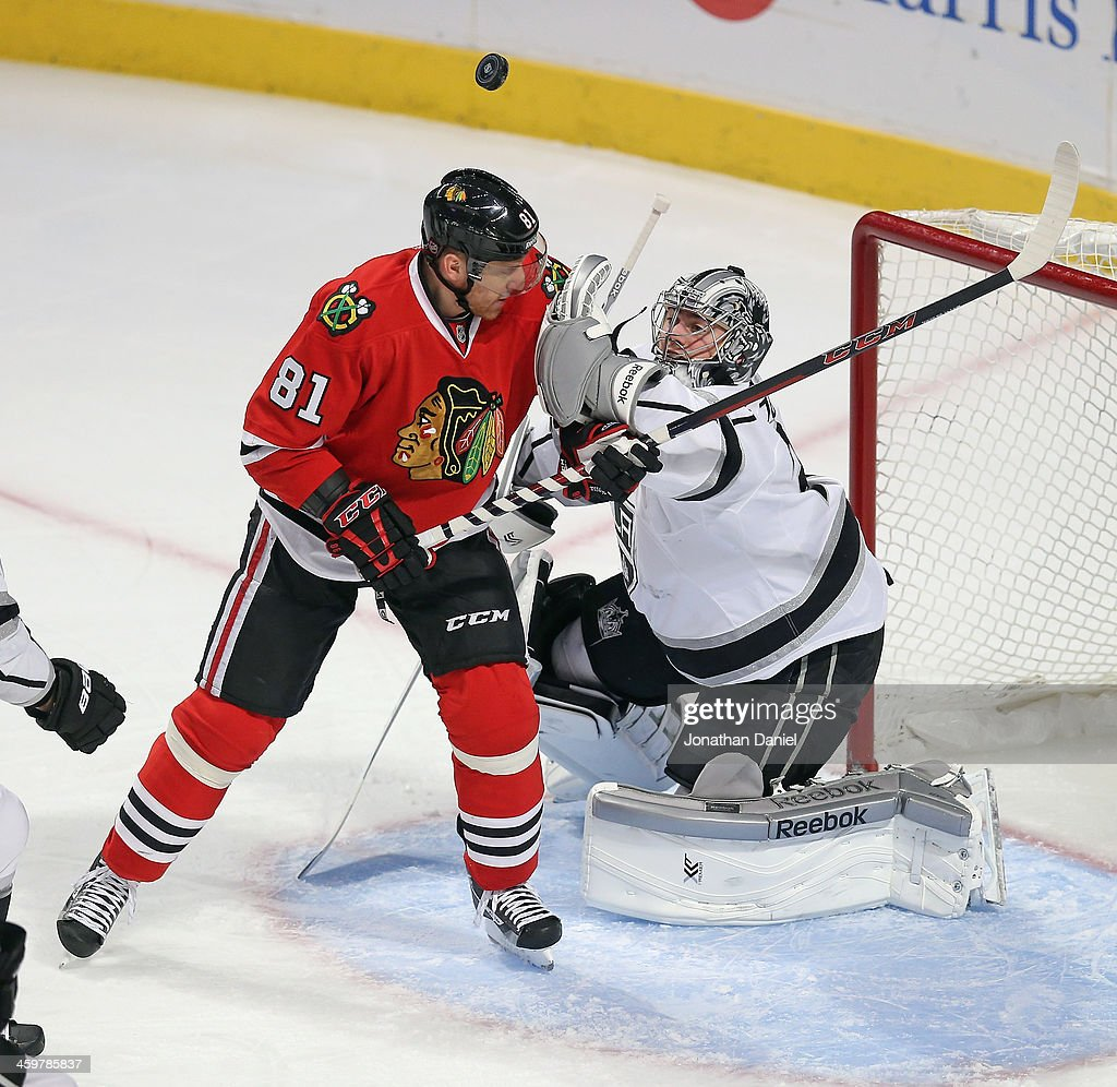 Martin Jones #31 of the Los Angeles Kings clears the puck over the head of <a gi-track='captionPersonalityLinkClicked' href=/galleries/search?phrase=Marian+Hossa&family=editorial&specificpeople=202233 ng-click='$event.stopPropagation()'>Marian Hossa</a> #81 of the Chicago Blackhawks as the puck slips away at the United Center on December 30, 2013 in Chicago, Illinois.