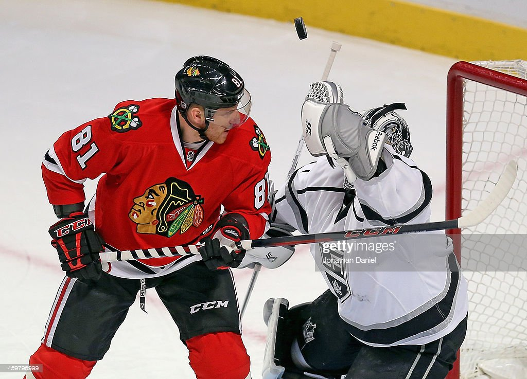 Martin Jones #31 of the Los Angeles Kings clears the puck over the head of <a gi-track='captionPersonalityLinkClicked' href=/galleries/search?phrase=Marian+Hossa&family=editorial&specificpeople=202233 ng-click='$event.stopPropagation()'>Marian Hossa</a> #81 of the Chicago Blackhawks as the puck slips away at the United Center on December 30, 2013 in Chicago, Illinois. The Blackhawks defeated the Kings 1-0.