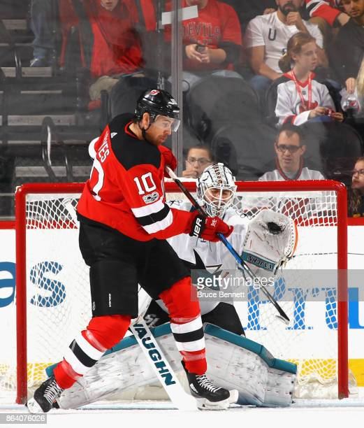 Martin Jones of the San Jose Sharks makes the save as Jimmy Hayes of the New Jersey Devils looks to deflect the puck during the first period at the...