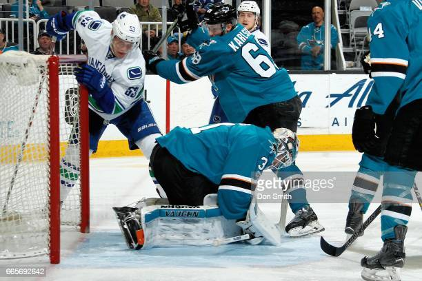 Martin Jones the San Jose Sharks covers the puck as Melker Karlsson of the San Jose Sharks defends against Bo Horvat of the Vancouver Canucks at SAP...