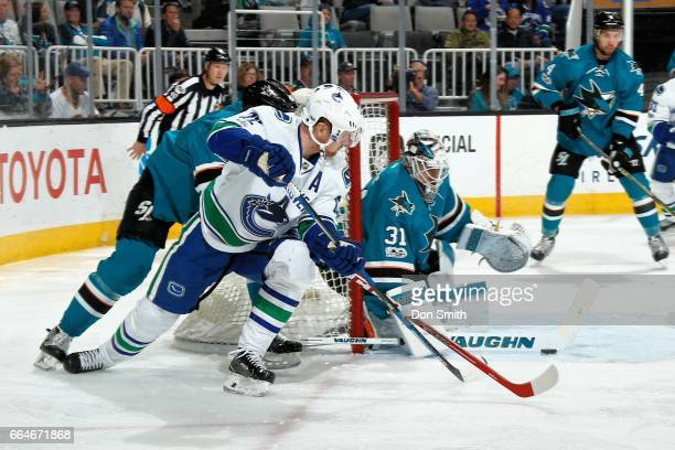 Martin Jones the San Jose Sharks makes a save as Daniel Sedin of the Vancouver Canucks looks during a NHL game at SAP Center at San Jose on April 4...
