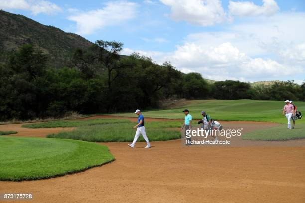 Martin Kaymer of Germany and Francesco Molinari of Italy cross a bunker on the 14th hole during the final round of the Nedbank Golf Challenge at Gary...